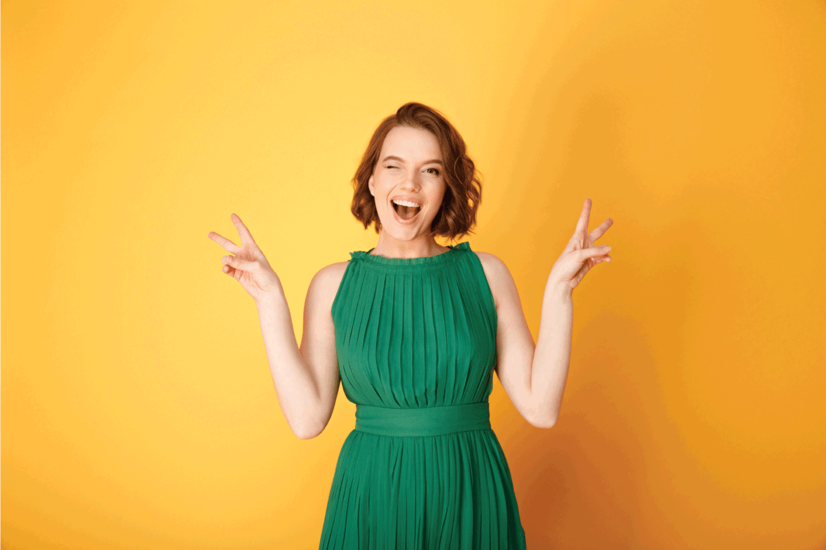 model in green dress striking a cute pose while winking on yellow background