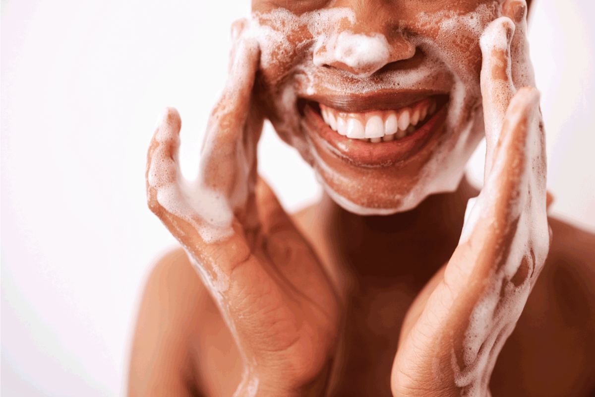 woman washing her face against a white background