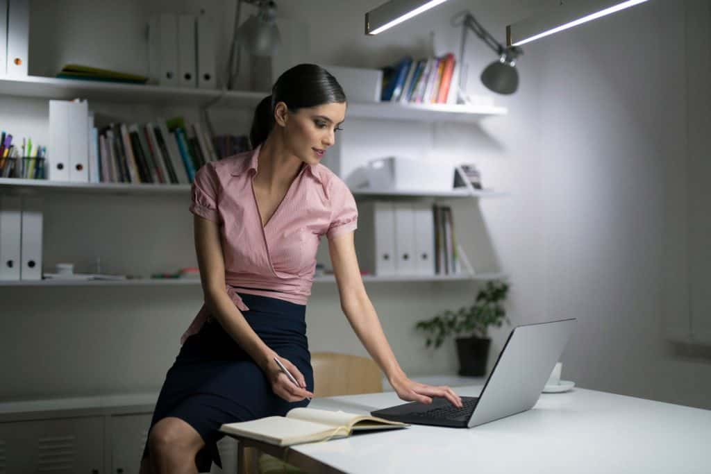 A beautiful business woman wearing a pink blouse and a black pencil dress, Can You Wear A Pencil Skirt To An Interview?