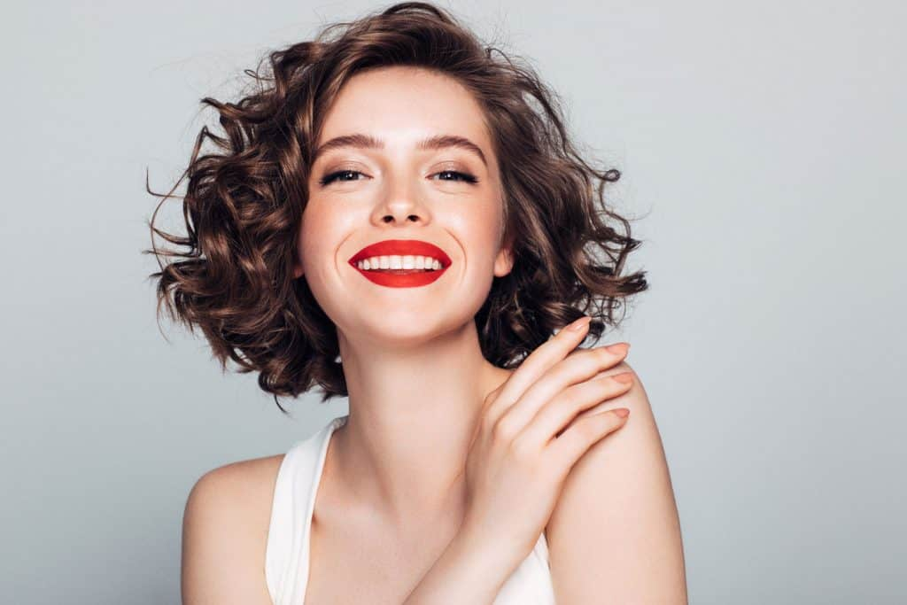 A beautiful curly haired woman wearing a white top and red lipstick, Does Red Lipstick Go With Everything?