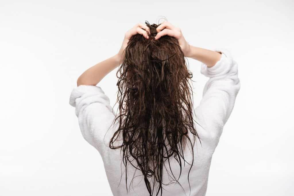 A beautiful woman wearing a white blouse and hold her wet hair