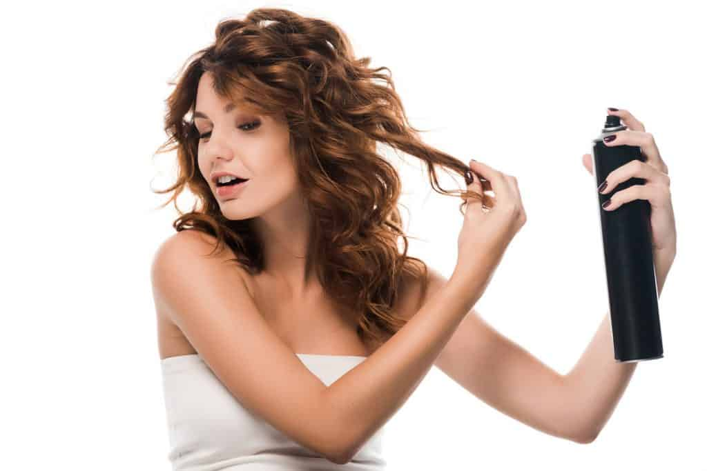 A brunette woman spraying hairspray on a white background