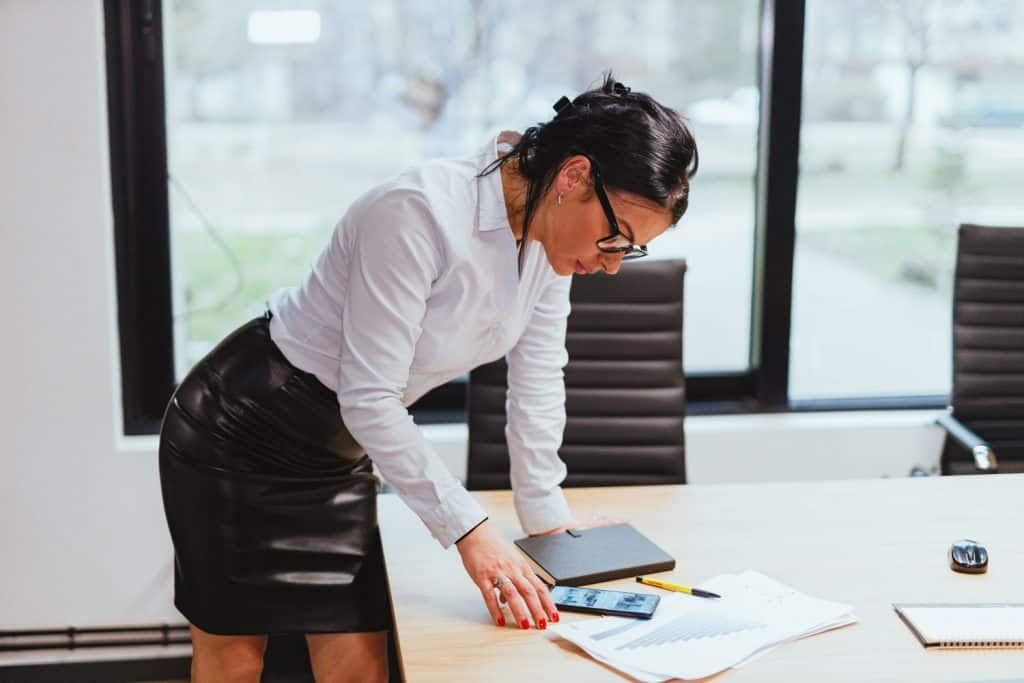 A business woman wearing a white blouse and a leather pencil skirt