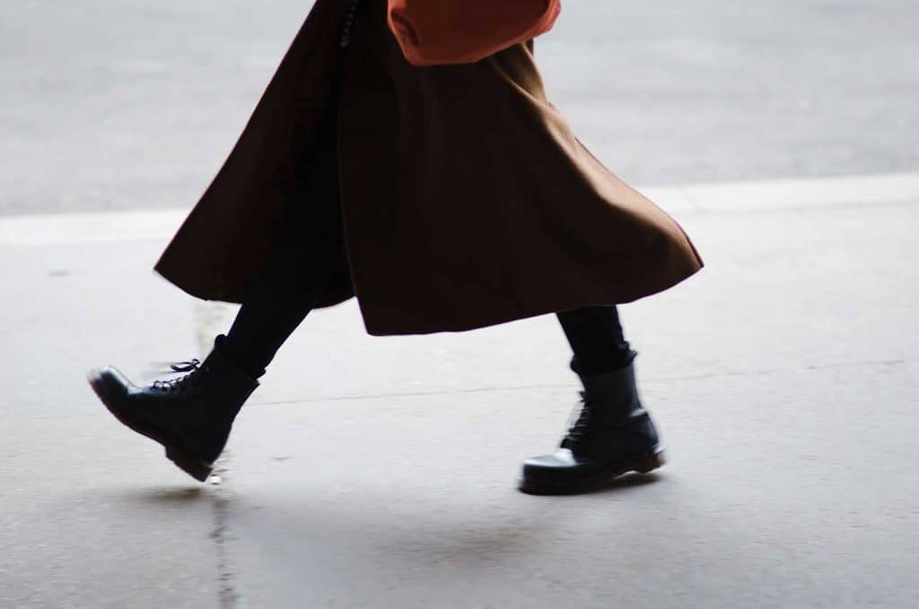 A fashionable woman wearing a long winter coat and thick funky boots walking by on the city streets