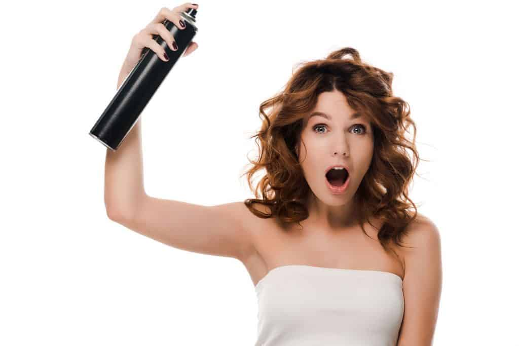 A happy woman spraying hairspray on her hair before heading for work