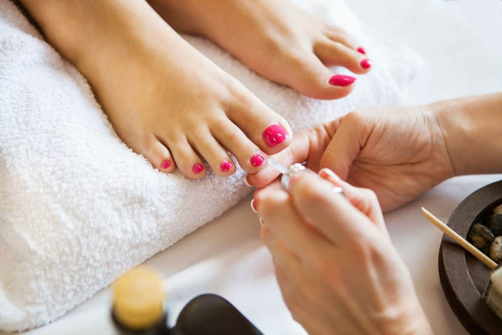 A pedicure artist applying nail polish on her clients nails using the color pink, Bottoms Of Feet Hurt After Pedicure - What To Do?