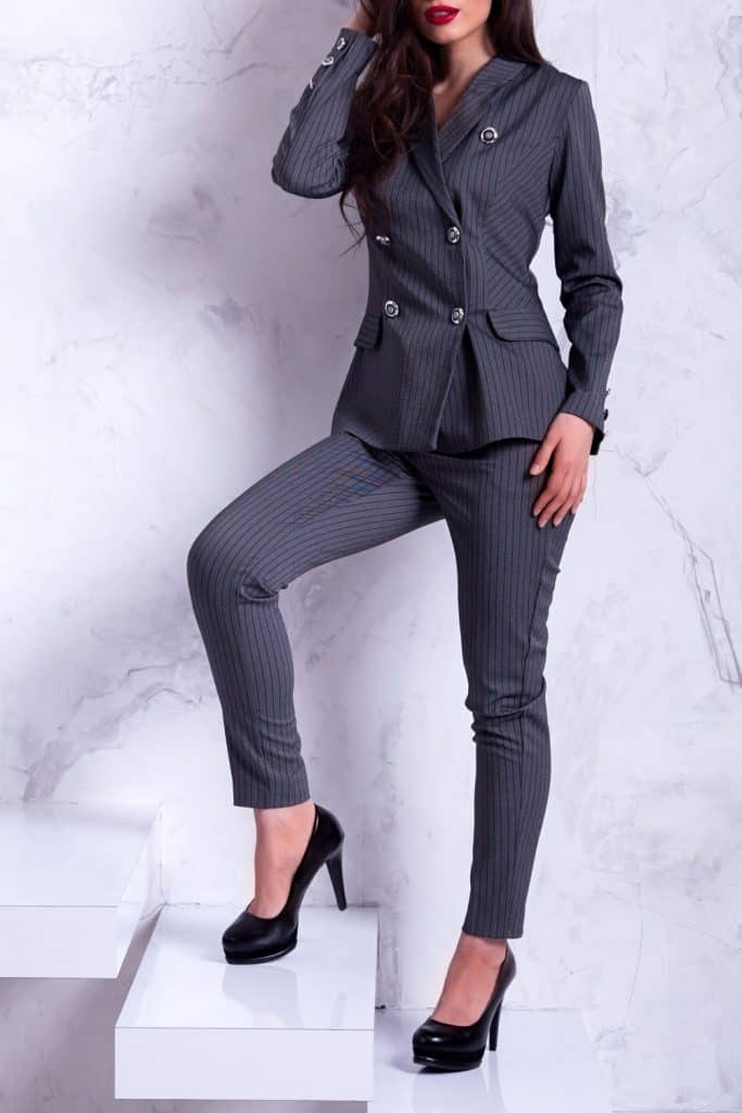 A tall beautiful business woman wearing a gray suit and tall black sandals
