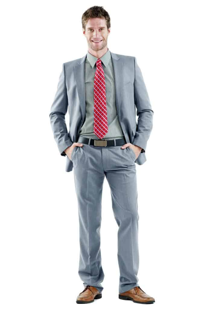 A tall business man wearing a gray suit on a white background