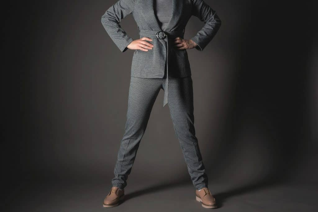 A tall business woman wearing a gray suit and black leather shoes on a dark gray background, What Color Shoes Go With A Gray Suit?