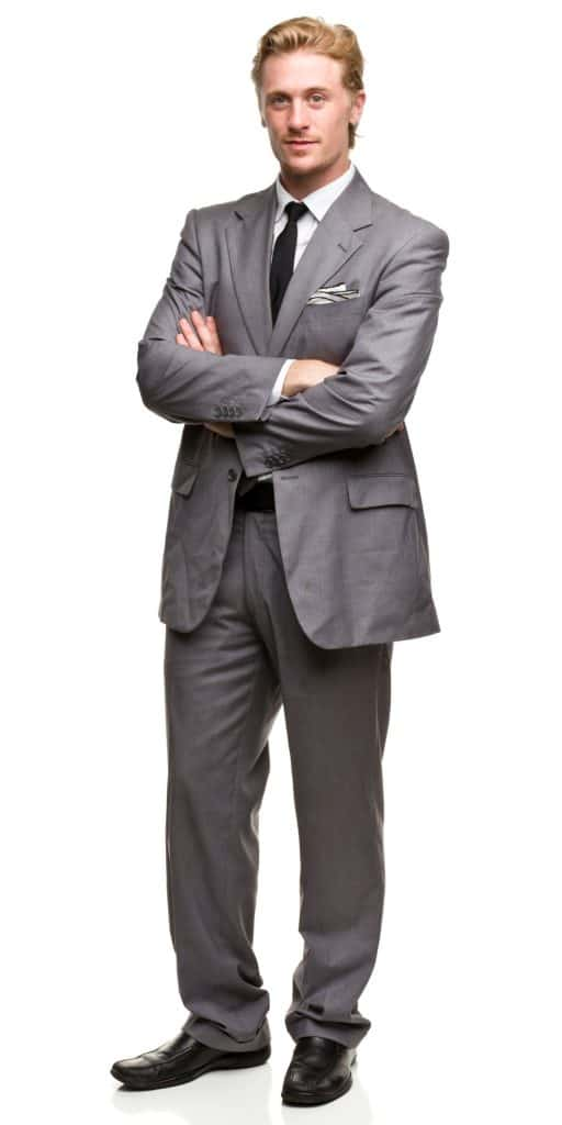 A tall businessman wearing a gray suit and black leather shoes on a white background