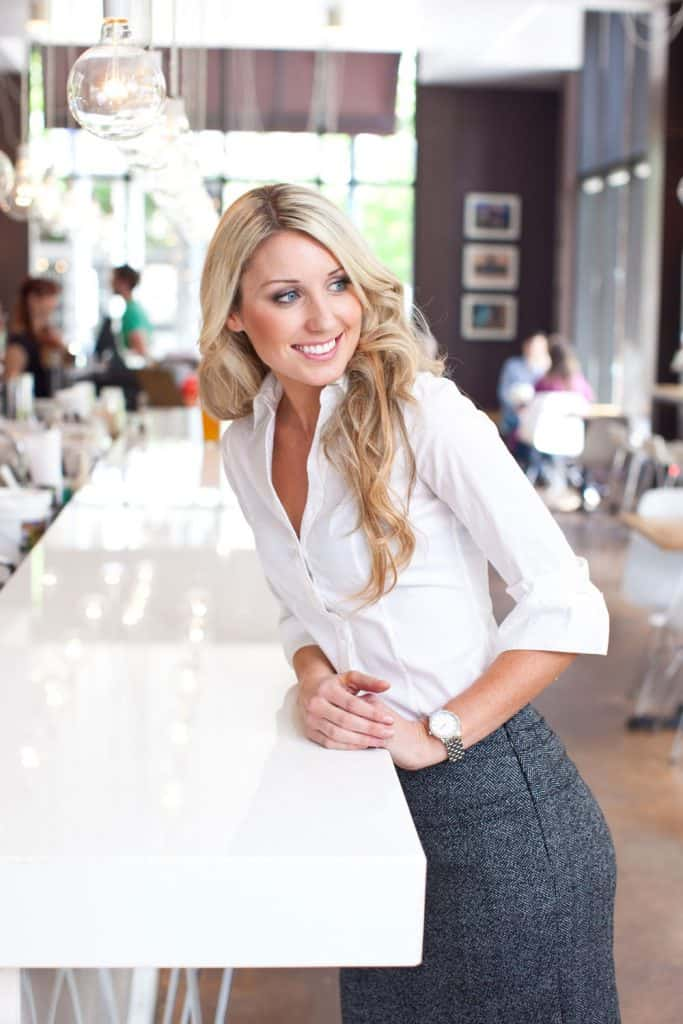 A tall young lady wearing a white blouse and gray pencil skirt leaning on the coffee shops bar stand