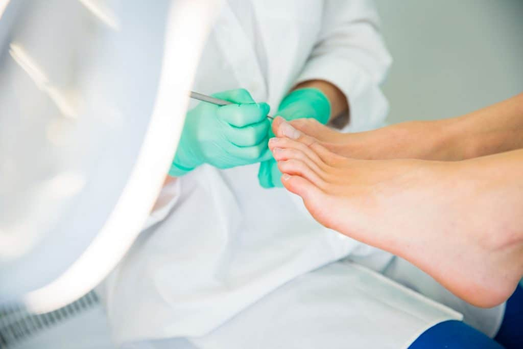 A woman doing a pedicure job on her client
