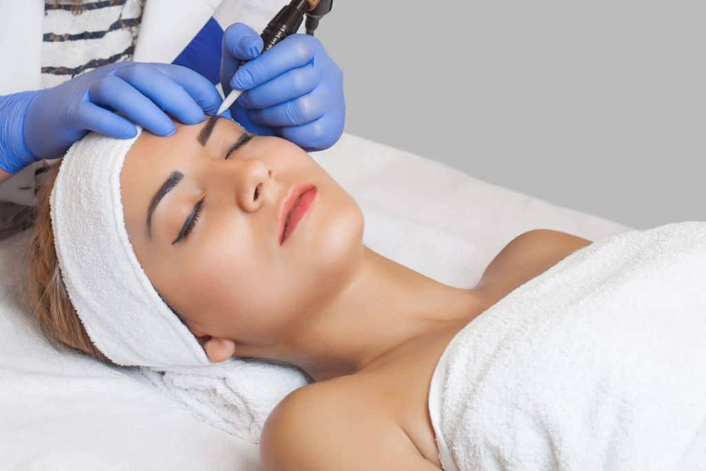 A woman getting her eyebrows done at the dermatologist, Are Microblading Eyebrows Permanent?