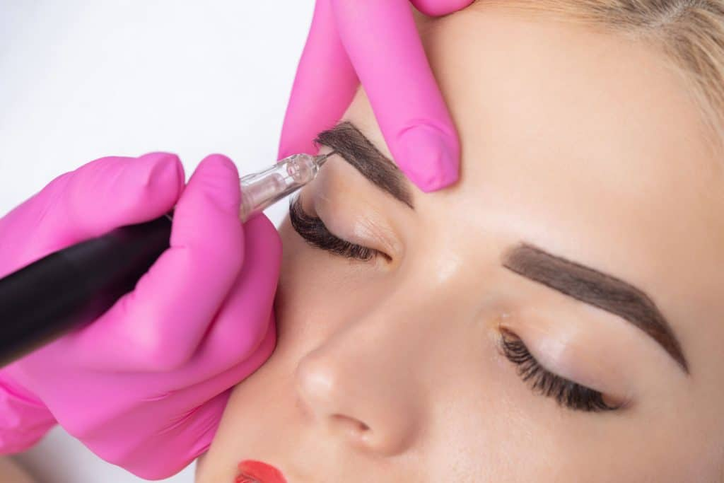A woman getting her eyebrows microbladed