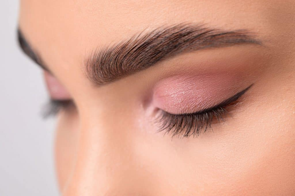 A woman showing her microblade eyebrows and pink colored eyelids