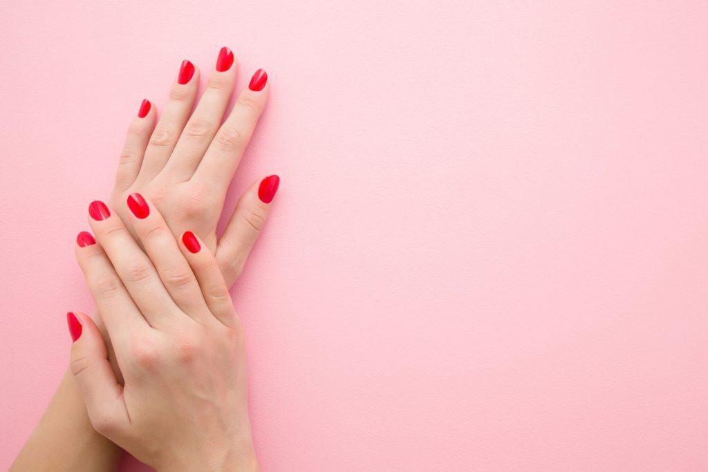 A woman showing her pale hand with red colored finger nails, What Nail Color For Pale Skin?