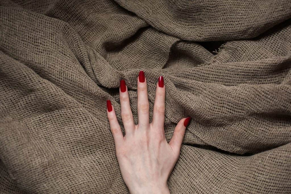 A woman showing her red polished nails on a burlap background