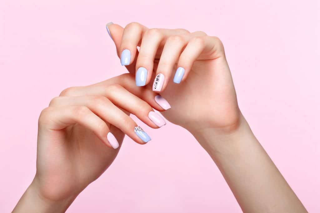 A woman showing her stylish nail art design on a pink background