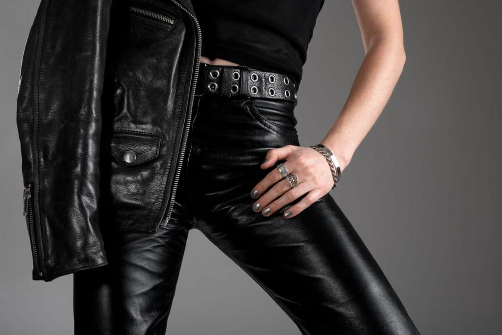 A woman wearing black leather pants and holding a black leather jacket