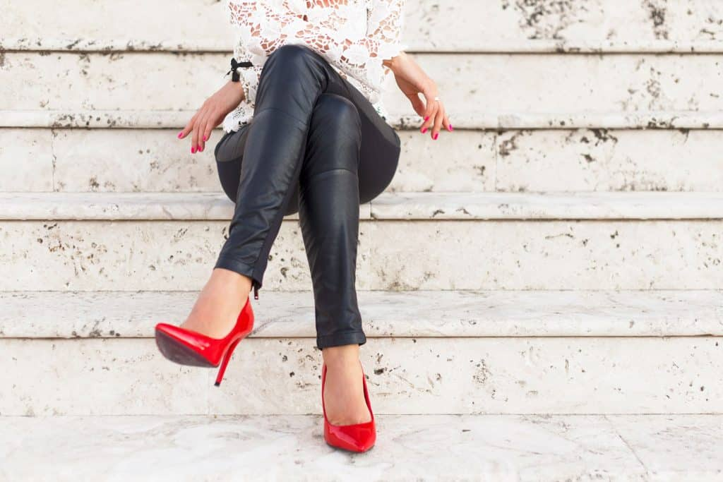 A woman wearing black leather pants, red shoes, and white blouse