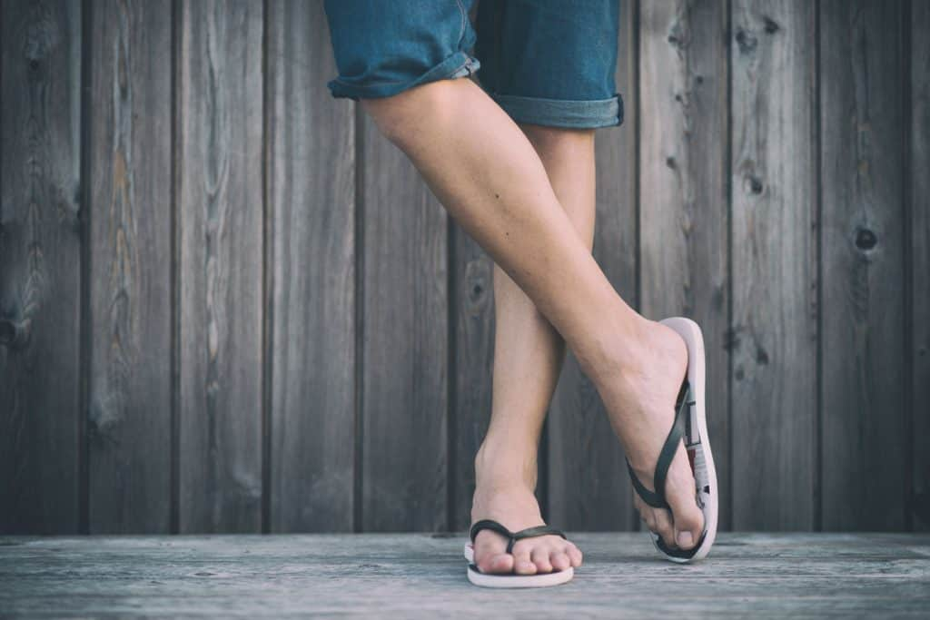 A woman wearing jean short and flip flops, How To Keep Flip Flops From Slipping Off