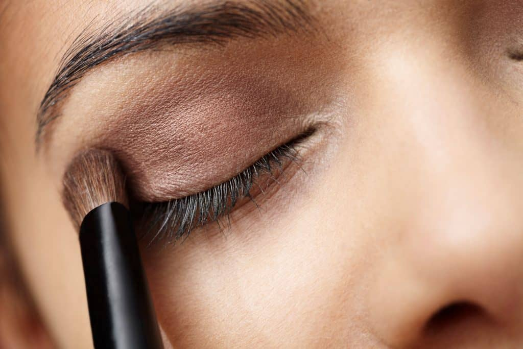 An up close photo of a woman applying brown eyeshadow, What Color Eyeshadow For Brown Eyes And Olive Skin?