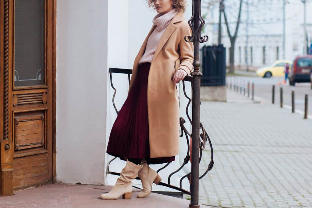 Attractive girl with curly blond hair, in a light coat and a warm sweater against the background of urban architecture, Can You Wear Tights With A Midi Skirt?