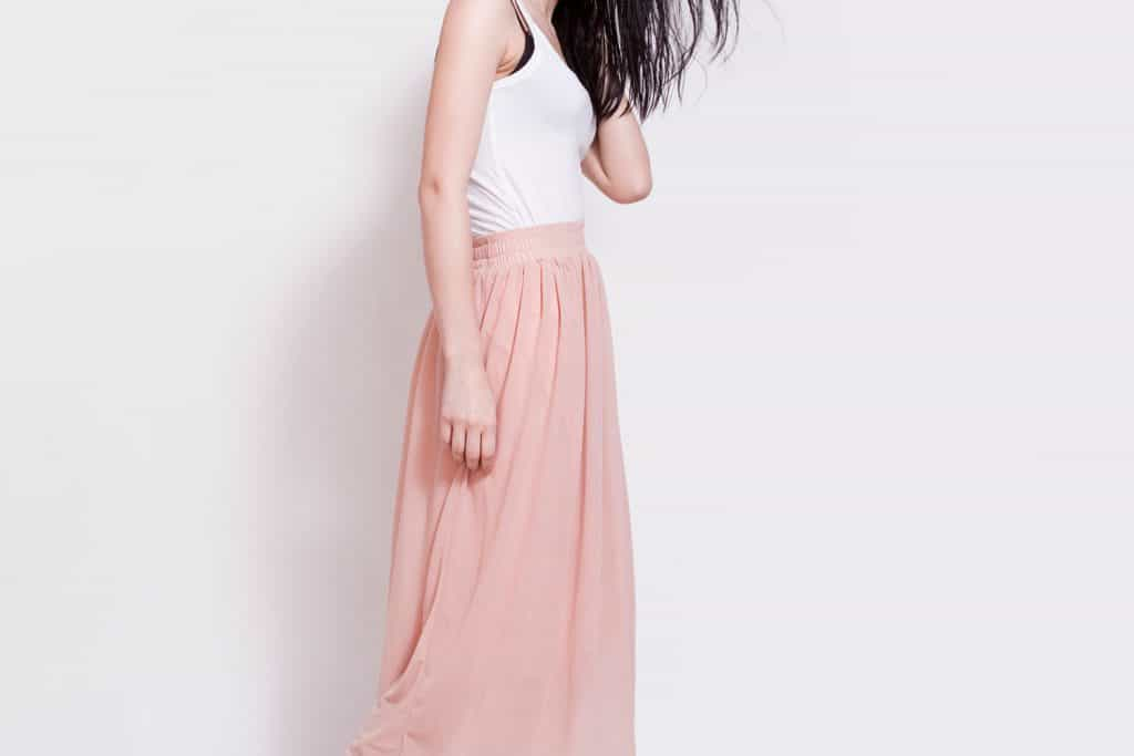 Attractive young brunette woman with perfect natural neutral make-up, freckles and simple hairstyle wearing high heels shoes, pink maxi skirt,white top and gray hat, Can You Wear A Maxi Skirt As A Dress? [Here's How]