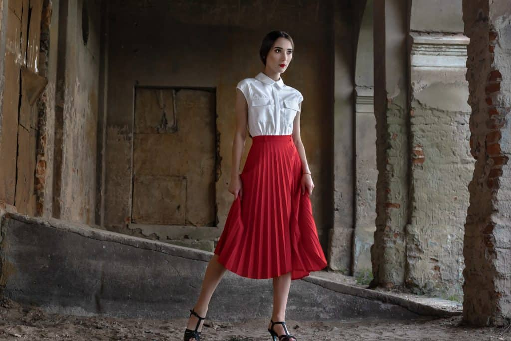 Beauty Fashion Model Girl with brown hair against the background of an old, abandoned building, in a stylish red skirt and shirt. Sexy woman portrait with perfect make up and fashion clothes. Beauty Trends