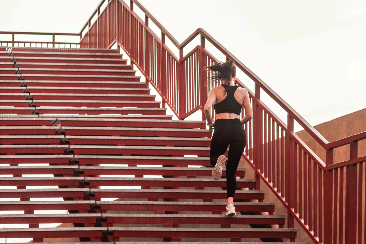 Back view of runner athlete, fit brunette girl in black sportswear, tight pants and top, running up stairs doing cardio training