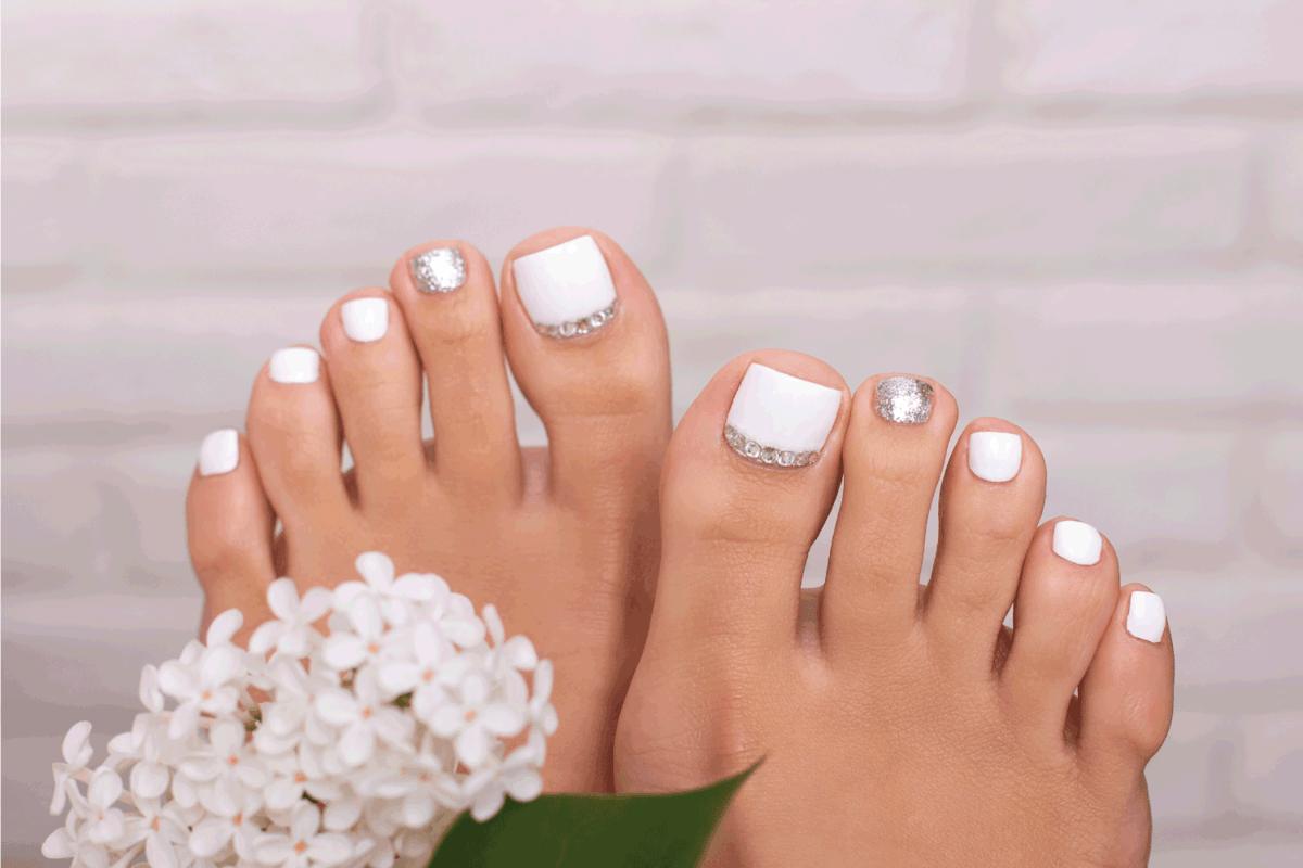 Beautiful female feet with fashion manicure nails, white an silver gel polish