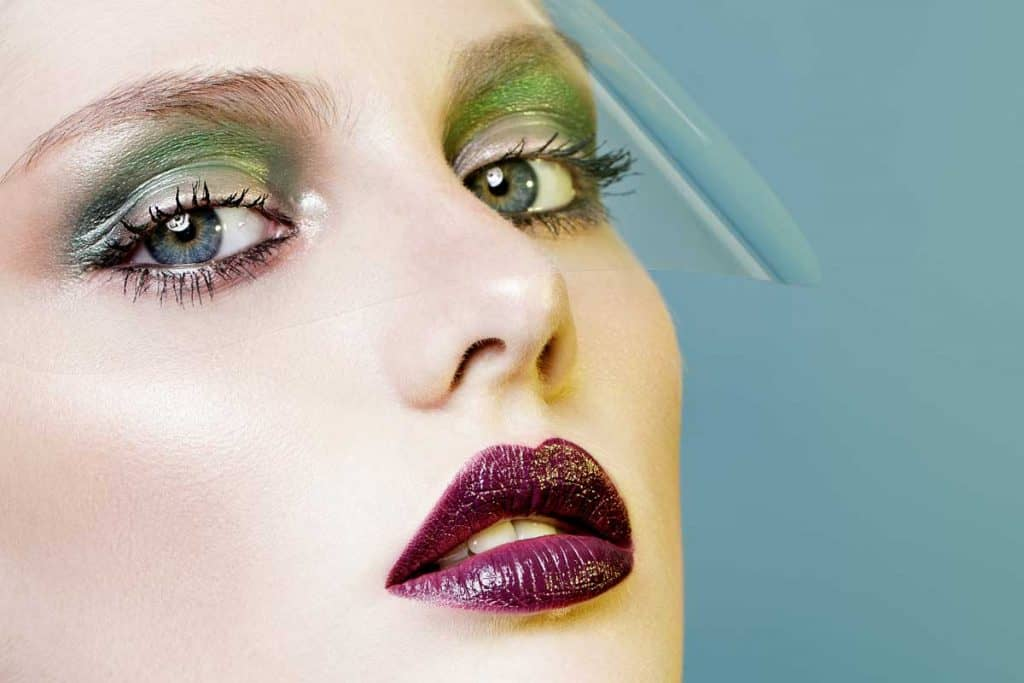 Beautiful girl with vinous lips and green eyeshadows on teal background, What Color Lipstick Goes With Green Eyeshadow?