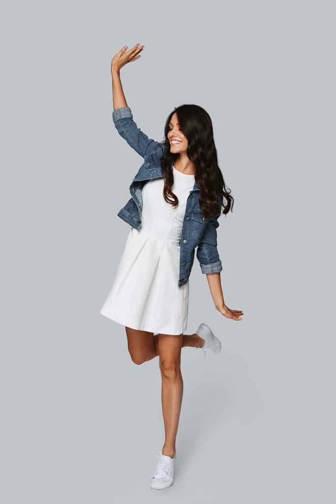 Beautiful young woman in white dress and denim jacket