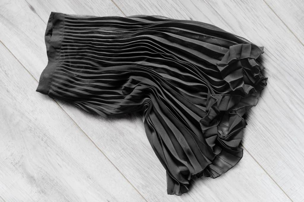 Black-chiffon-pleated-midi-skirt-lying-on-white-wooden-background,-Can-You-Wear-Tights-With-A-Midi-Skirt