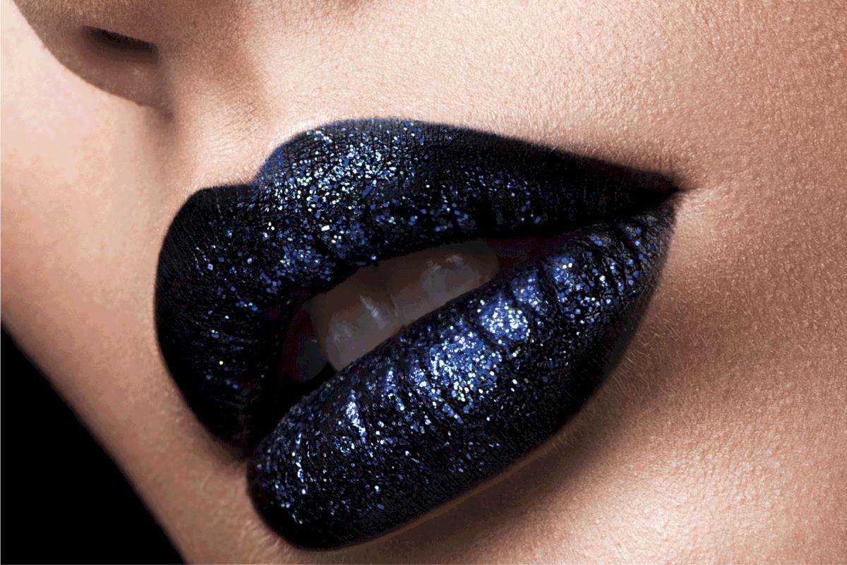 Brilliant glossy lips closeup. Purple glitter on black lipstick.