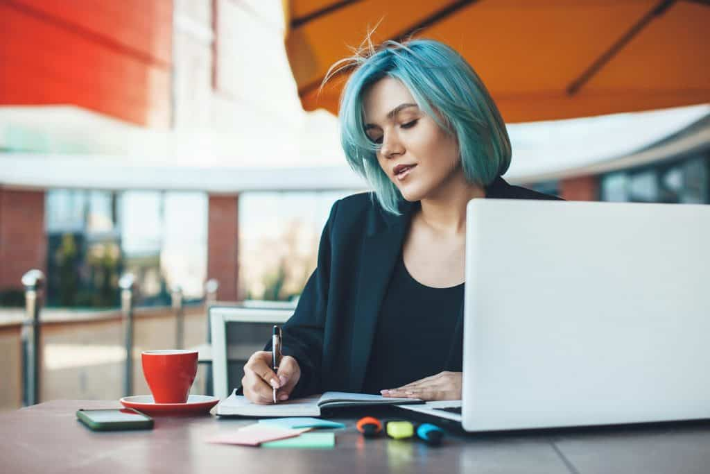 Caucasian entrepreneur with blue hair working in a cafeteria