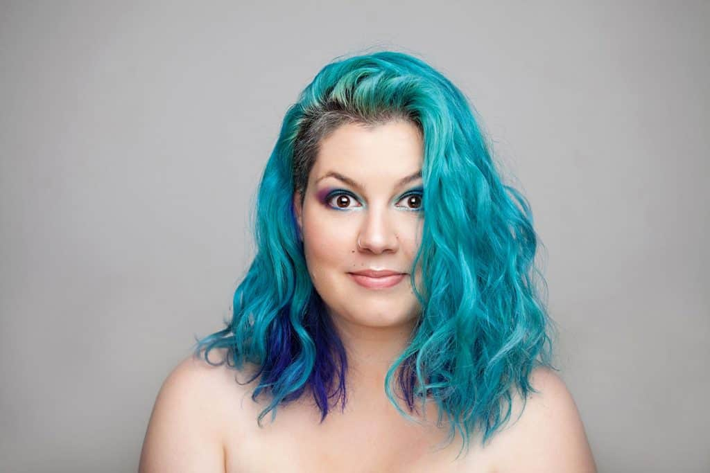 Cheerful young woman with blue hair looking at the camera