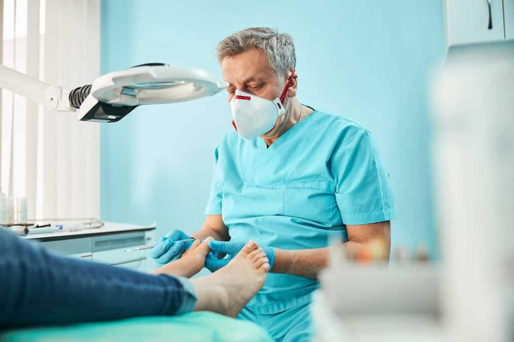 Chiropodist podiatrist in blue uniform and gloves with medical tool in hand while doing treatment procedure on feet