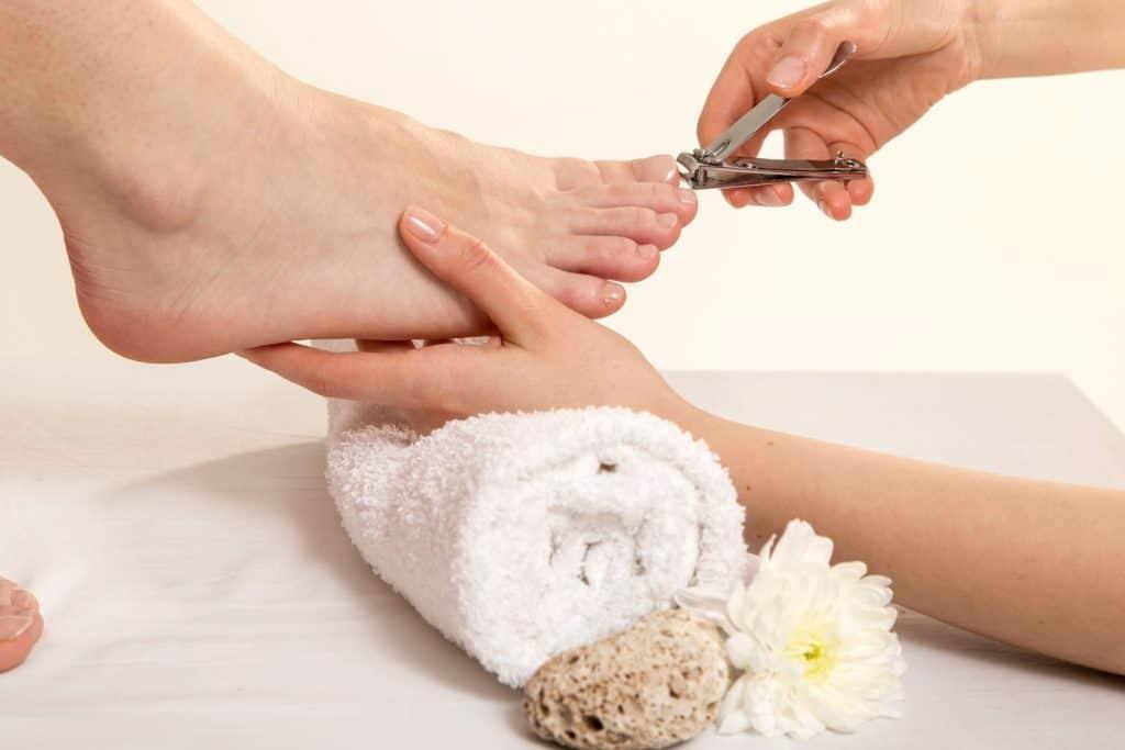 Close up View Of A Beautician's Hand Cutting Client's Toenails, Should You Cut Your Toenails Before A Pedicure?