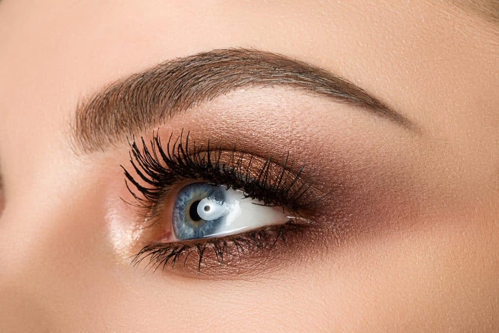 Close up of blue eyed woman with beautiful brown shade smokey eye makeup