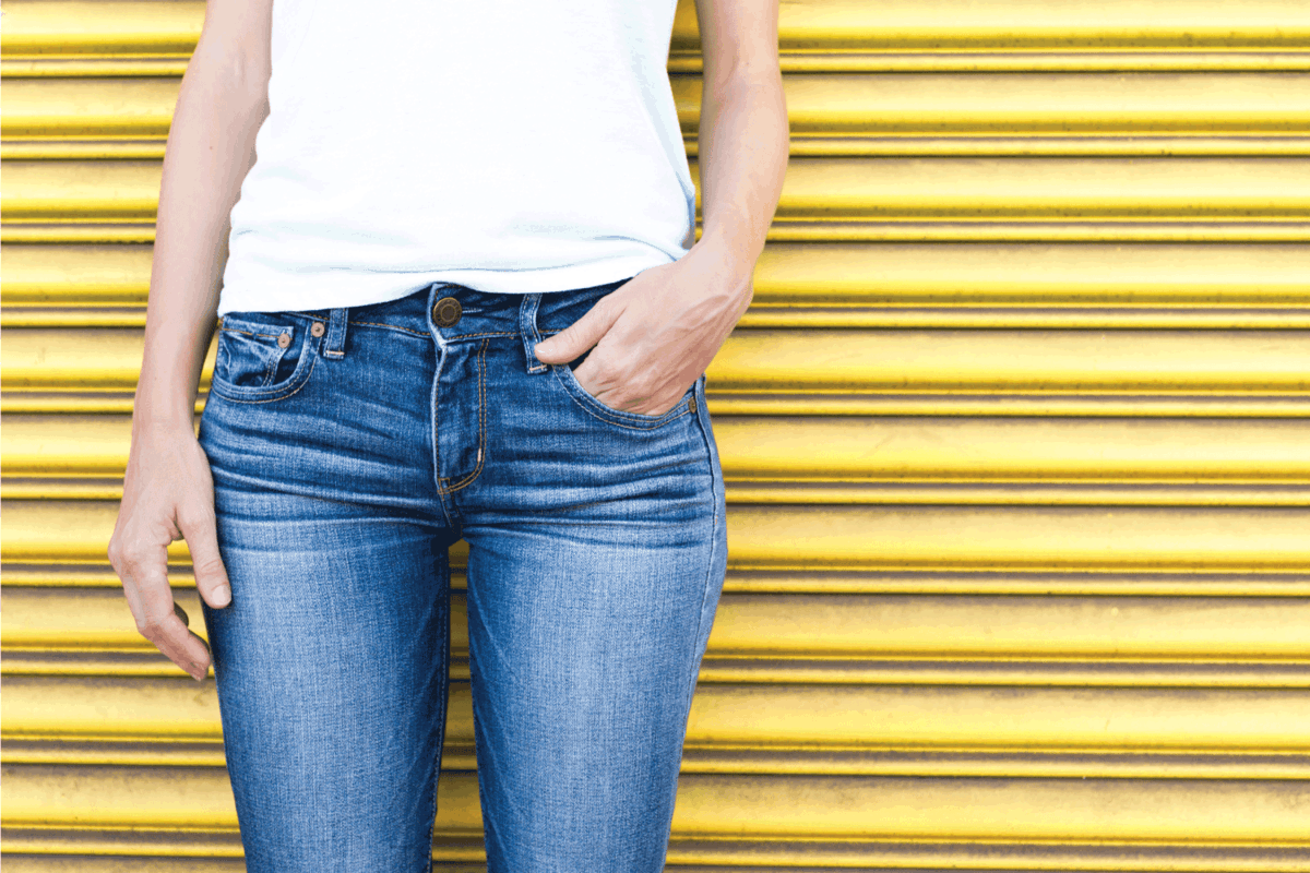 Closeup of female wearing jeans and white shirt against yellow background. Do Skinny Jeans Make You Look Taller Or Shorter