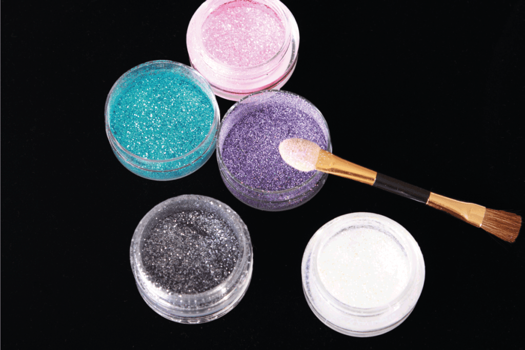 Colored glitter for makeup in small containers. How Long Does Body Glitter Stay On Your Body [And How To Remove It]