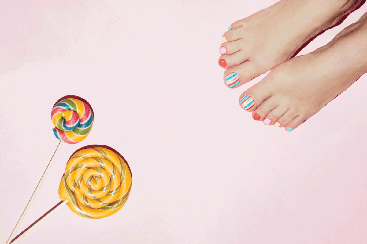 Colorful stylish summer pedicure and sugar hard candy on a pink background.