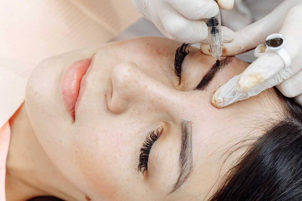 Cosmetologist in white gloves tattooing eyebrows of a woman in beauty salon