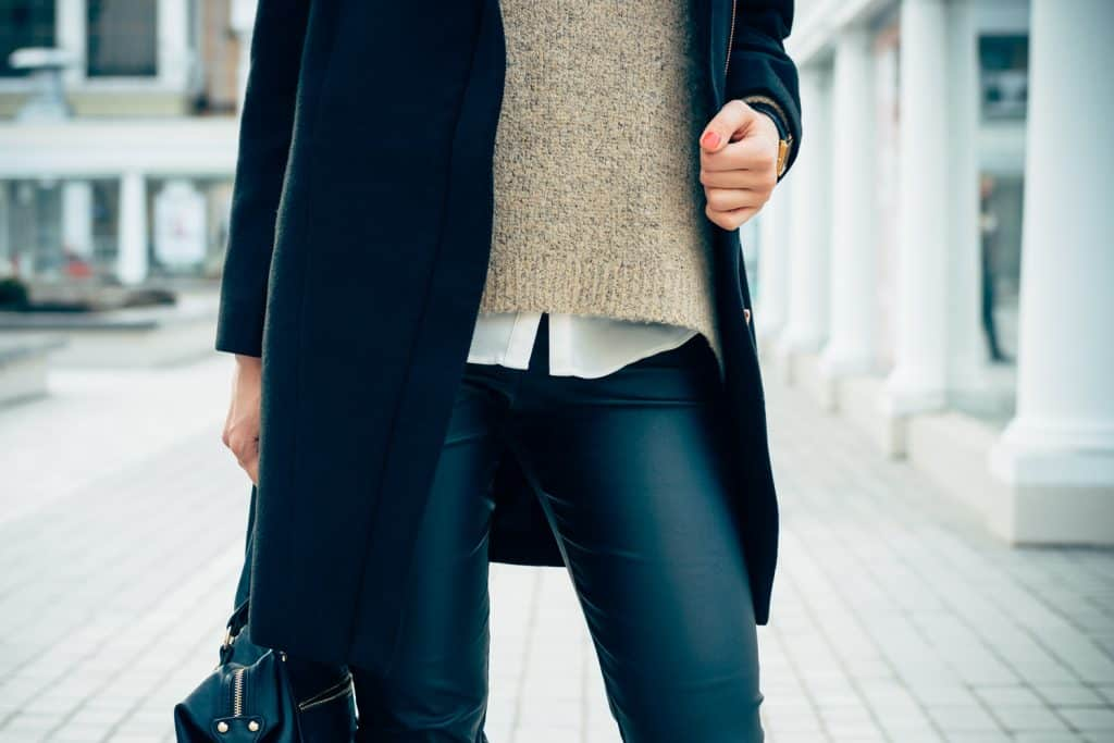 Details of women's clothing. Close-up of a woman in a sweater, coat, black pants. In her hand female bag.