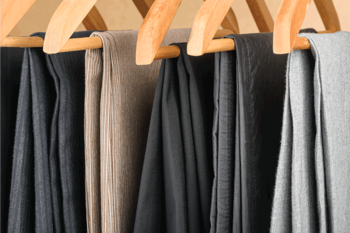 Different types of chinos pants on wooden hangers
