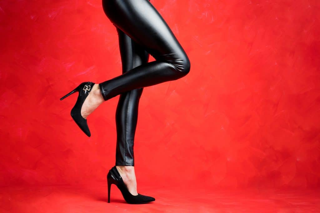 Fashion model with beautiful legs wearing black leather pants and black high heel shoes on red background
