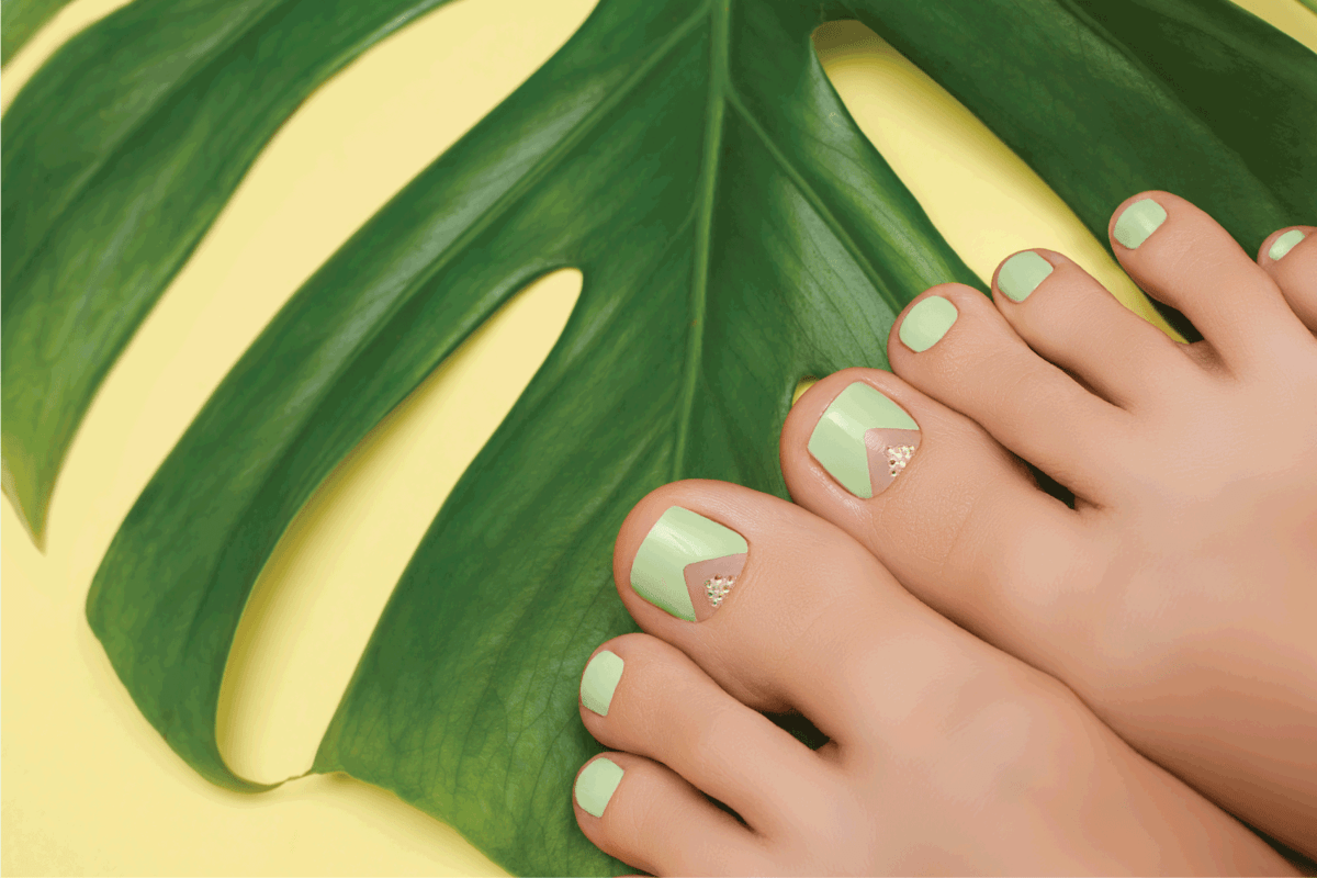 Female feet with green nail design. Green nail polish pedicure on yellow background