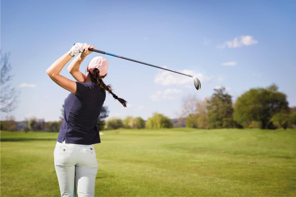 Female golf player swinging golf club.