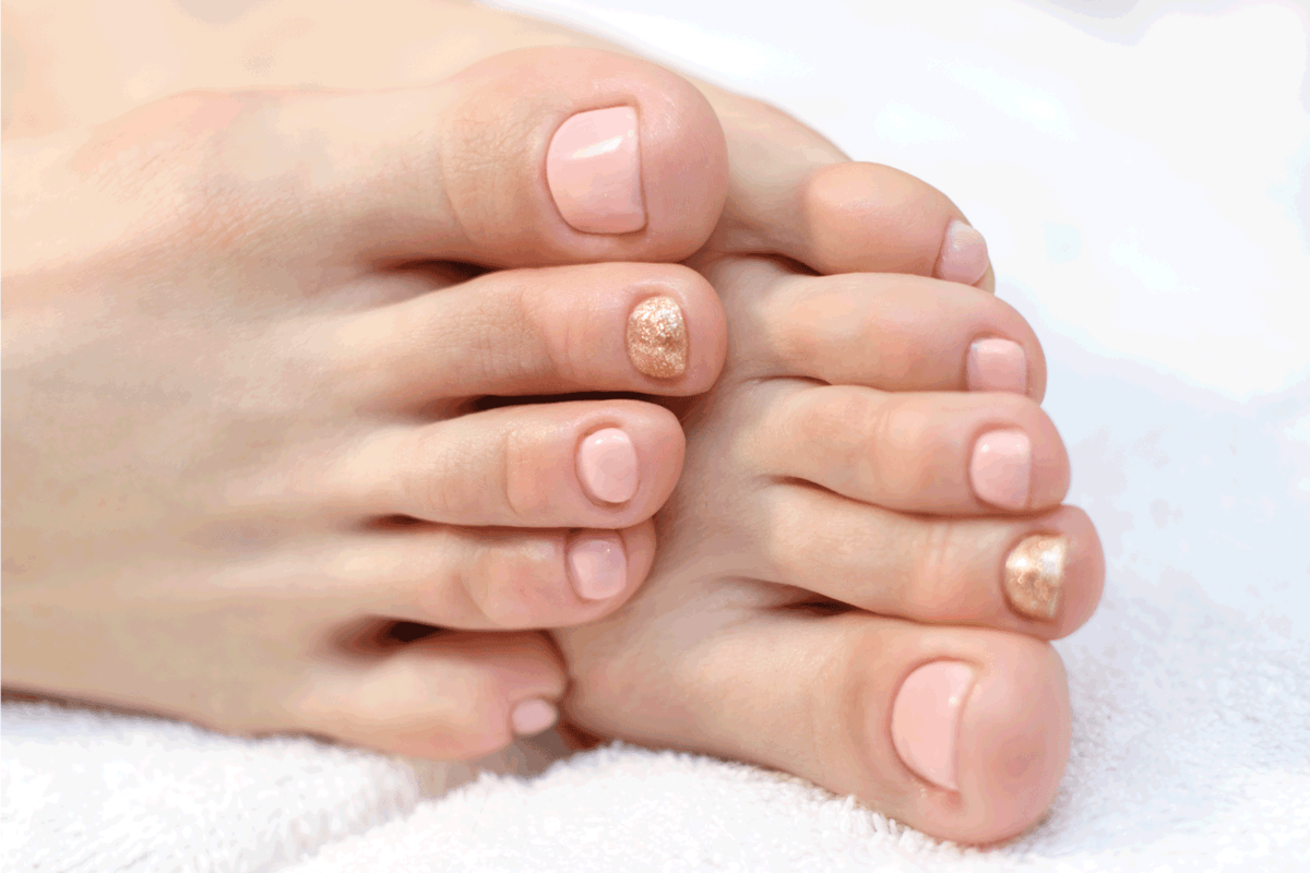 Female pedicure in pink with gold on a white towel. Toes close-up.